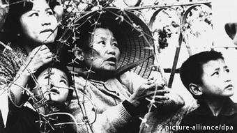 A woman with her children is seen behind barbed wire in February 1968. (Photo: picture-alliance/ dpa)