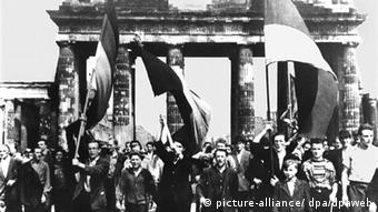 Das Archivbild vom 17.06.1953 zeigt Ost-Berliner, die mit wehenden Fahnen vom Ost-Sektor aus durch das Brandenburger Tor marschieren (Archivfoto). Über den Ausgang der Bundestagswahl am 6. September 1953 muss sich Bundeskanzler Adenauer keine Sorgen machen: Der Wahlkampf 1953 wird überschattet vom Aufstand in der DDR am 17. Juni, die Wähler im Westen glauben nicht mehr an die Versprechen der SED und der Sowjetunion zur Wiedervereinigung - und mit der Angst vor der kommunistischen Bedrohung wächst die Zustimmung für Adenauers Politik in der Westbindung. (nur s/w) (zur Serie Bundestagswahl historisch - Teil 2: 1953 vom 25.07.2005) +++(c) dpa - Bildfunk+++