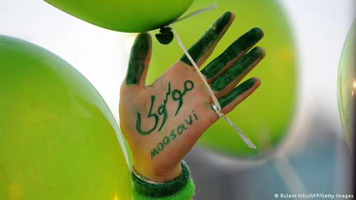 : A supporter of Iranian Presidential candidate Mir Hossein Mousavi shows a hand reading 'Moosavi' during a protest against the election results in Iran on June 28, 2009, on Taksim Square in Istanbul along with other demonstrators holding green balloons. AFP PHOTO/BULENT KILIC (Photo credit should read BULENT KILIC/AFP/Getty Images) FREI FÜR SOCIAL MEDIA