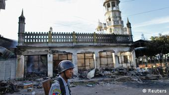 A police officer stands near a mosque which was burnt during a riot between Buddhist and Muslims in Lashio township May 29, 2013. (Photo: REUTERS/Soe Zeya Tun)