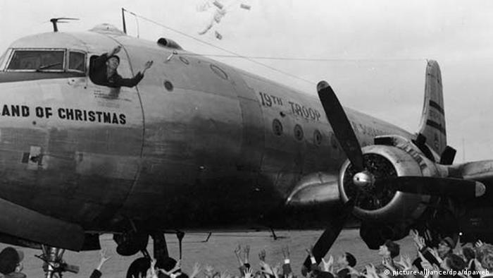 Pilot Gail S. Halvorsen wirft 1948 auf dem Flughafen Berlin-Tempelhof amerikanische Süßigkeiten aus seinem Transportflugzeug, die von Kindern auf dem Flugfeld aufgefangen werden (c) dpa - Report
