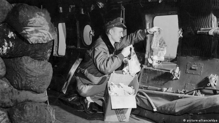 Gail Halvorsen wirft Schokolade und Kaugummis an selbstgebastelten kleinen Fallschirmen aus einem Rosinenbomber über Berlin ab. (Foto: dpa)