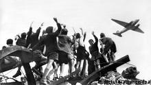 West-Berliner Jungen, die auf einem Trümmerberg stehen, begrüßen winkend ein US-amerikanisches Transportflugzeug, das Versorgungsgüter nach West-Berlin bringt (Aufnahme von 1948). Die UdSSR verhängte am 24.6.1948 als Reaktion auf die Währungsreform in den Westsektoren eine Blockade. Alle Land- und Wasserwege wurden für den Personen- und Güterverkehr zwischen Westberlin und Westdeutschland gesperrt. Die Versorgung der Westberliner Bevölkerung und der westalliierten Besatzung erfolgte daraufhin durch eine von den USA und Großbritannien errichtete Luftbrücke. Von Juni 1948 bis September 1949 brachten die Maschinen rund 2,3 Millionen Tonnen Hilfsgüter in die Stadt. 76 Menschen kamen dabei ums Leben. Mit Feierlichkeiten in Berlin wird in diesen Tagen des 50. Jahrestages der Luftbrücke gedacht.