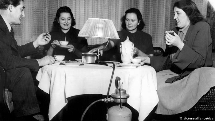 Eine Familie sitzt um einen Tisch mit einer Lampe, die mit Propangas betrieben wird (Foto: dpa)
