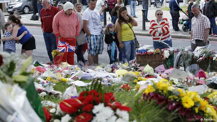 People look at messages and flowers left for British soldier Lee Rigby, at the scene of his murder in Woolwich, southeast London May 27, 2013. One of two men arrested over the murder of a British soldier in a London street was detained in Kenya in 2010 on suspicion of seeking to train with an al Qaeda-linked group in Somalia, Kenyan police said on Sunday. REUTERS/Olivia Harris (BRITAIN - Tags: CRIME LAW MILITARY POLITICS SOCIETY) // eingestellt von se
