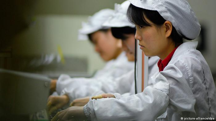 Workers on an assembly line at a Foxconn factory in China (picture-alliance/dpa)