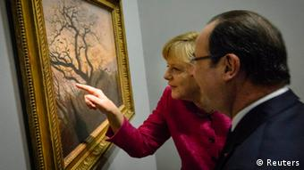 German Chancellor Angela Merkel draws the attention of French President Francois Hollande to a detail on the painting The Tree of Crows (Kraehen auf einem Baum) by Caspar David Friedrich as they visit the exhibition De l'Allemagne at the Louvre museum in Paris May 30, 2013. REUTERS/Bundesregierung/Steffen Kugler