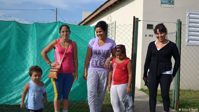 Griselda Alderete stands outside her home in La Perla with two of her children.