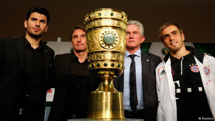 Bayern Munich's coach Jupp Heynckes (2nd R), team captain Phillip Lahm (R), VfB Stuttgart's coach Bruno Labbadia (2nd L) and team captian Serdar Tasci pose next to the German soccer cup (DFB Pokal) trophy during a news conference in Berlin May 31, 2013. Bayern Munich and VfB Stuttgart play the German soccer cup (DFB Pokal) final match on Saturday at the Olympic Stadium in Berlin. REUTERS/Tobias Schwarz (GERMANY - Tags: SPORT SOCCER)