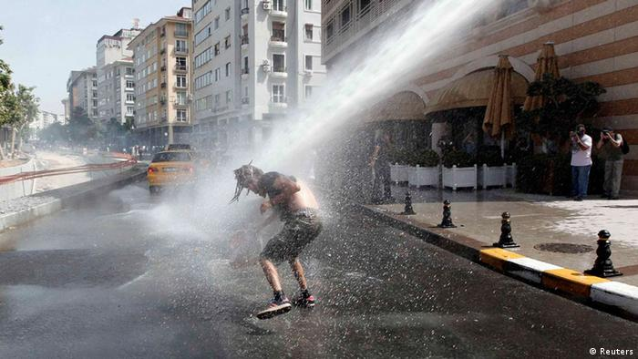 A demonstrator is hit by water cannon used by riot police to disperse the crowd during a protest against the destruction of trees in a park brought about by a pedestrian project, in Taksim Square in central Istanbul May 31, 2013. REUTERS/Osman Orsal (TURKEY - Tags: POLITICS CIVIL UNREST ENVIRONMENT CRIME LAW)