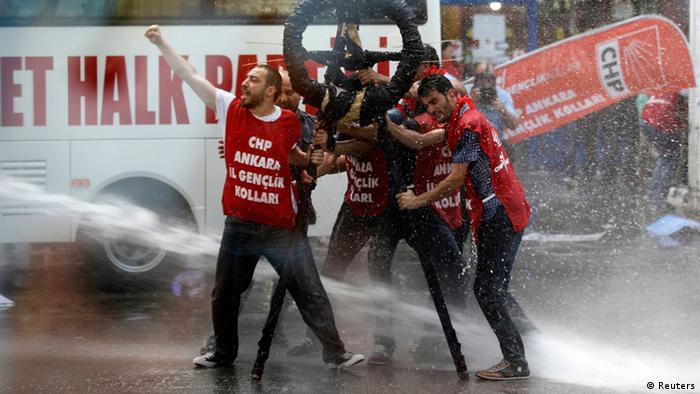Riot police use a water cannon to disperse demonstrators during a protest against Turkey's Prime Minister Tayyip Erdogan and his ruling Justice and Development Party (AKP) in central Ankara May 31, 2013. Thousands of demonstrators massed on streets surrounding Istanbul's central Taksim Square, long a venue for political unrest, while protests erupted in the capital Ankara and the Aegean coastal city of Izmir. The words on the men's shirts read, People's Republican Party (CHP) Young Members Group. REUTERS/Umit Bektas (TURKEY - Tags: POLITICS CIVIL UNREST TPX IMAGES OF THE DAY)