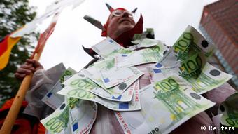 A protestor, calling himself a Capitalism Devil and wearing a costume made of fake 100 Euro notes, waits for the anti-capitalism Blockupy demonstration to begin in Frankfurt June 1, 2013. Thousands of demonstrators from the anti-capitalist Blockupy movement cut off access to the European Central Bank in Frankfurt to protest against policymakers' handling of Europe's debt crisis. REUTERS/Kai Pfaffenbach (GERMANY - Tags: CIVIL UNREST BUSINESS POLITICS)