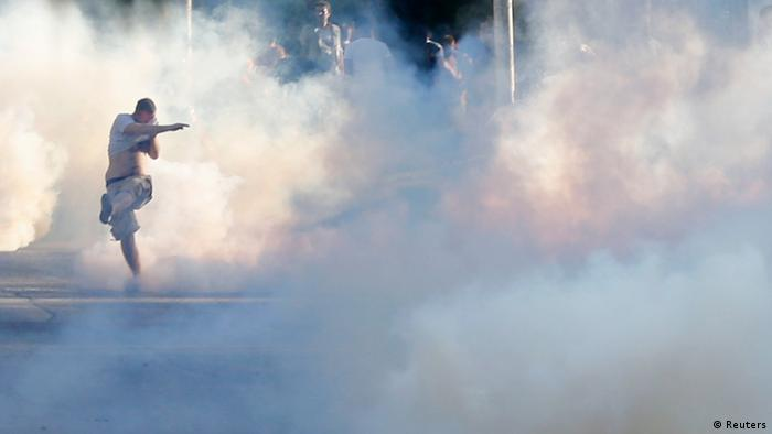 A demonstrator, tear gas (photo: Reuters)