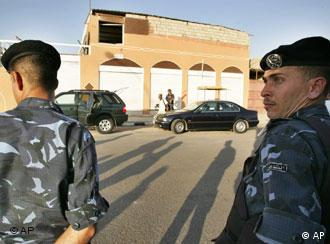 Two Jordanian policemen stand guard near a warehouse in Jordan's port town of Aqaba, from where attackers fired three Katyusha rockets early Friday, Aug. 19, 2005, killing a Jordanian soldier. One rocket narrowly missed a U.S. Navy ship docked in the Jordanian port and another fell close to a nearby airport inside neighboring Israel, officials said. The rocket fire narrowly missed the USS Ashland, an amphibious vessel attached to the Marines, in the Jordanian Red Sea port of Aqaba, marking the most serious attack on an American naval vessel since the 2000 bombing of the USS Cole in Yemen that killed 17 sailors. (AP Photo/ Nader Daoud)