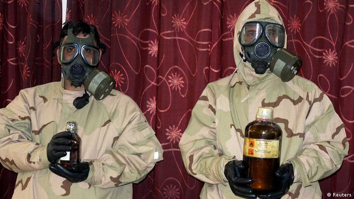 Soldiers wearing gas masks hold bottles containing chemical materials during a news conference at the Defence Ministry in Baghdad June 1, 2013. The materials were confiscated from four men who have been arrested, and are accused of planning to make chemical weapons like nerve and mustard gas, according to the ministry. REUTERS/Stringer (IRAQ - Tags: CIVIL UNREST CRIME LAW)