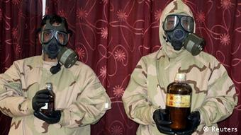 Soldiers wearing gas masks hold bottles containing chemical materials during a news conference at the Defence Ministry in Baghdad.