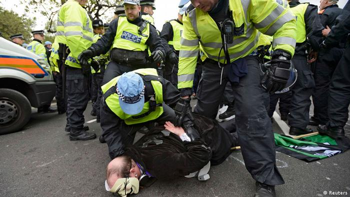 Police officers detain a supporter of a Unite Against Fascism (UAF) counter-demonstration near another protest held by the far-right British National Party (BNP) against the killing of a British soldier, in central London June 1, 2013. Police kept apart a small group of far-right protesters and a much larger anti-racist crowd in London on Saturday to stop them from coming to blows over how to respond to the killing of a soldier on a busy street last week. REUTERS/Dylan Martinez (BRITAIN - Tags: POLITICS CRIME LAW)