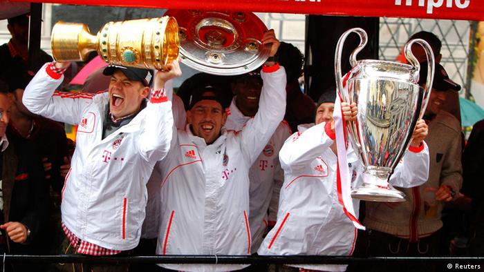 Bayern Munich's goalkeeper Manuel Neuer (L-R), Franck Ribery and Bastian Schweinsteiger hold up German soccer cup (DFB Pokal), German soccer championship Bundesliga and Champions League trophies as they make their way in a parade to the town hall with their three soccer trophies in Munich June 2, 2013. Bayern Munich completed the treble by beating VfB Stuttgart 3-2 in the German Cup final on June 1, 2013, adding the trophy to the Champions League and Bundesliga titles they have already won this season. REUTERS/Michaela Rehle (GERMANY - Tags: SPORT SOCCER)