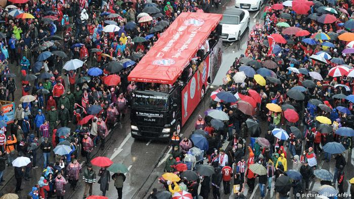 Bayern's team bus tours the streets of Munich (02.06.2013) in heavy rain as the team celebrates its treble - fans line the streets, almost all of them holding umbrellas. (Photo via Tobias Hase/dpa)