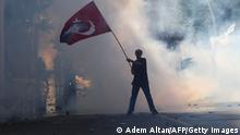 Tear gas surrounds a protester holding a Turkish flag with a portrait of the founder of modern Turkey Mustafa Kemel Ataturk during an anti-government demonstration in Ankara on June 1, 2013 (Adem Altan/AFP/Getty Images)