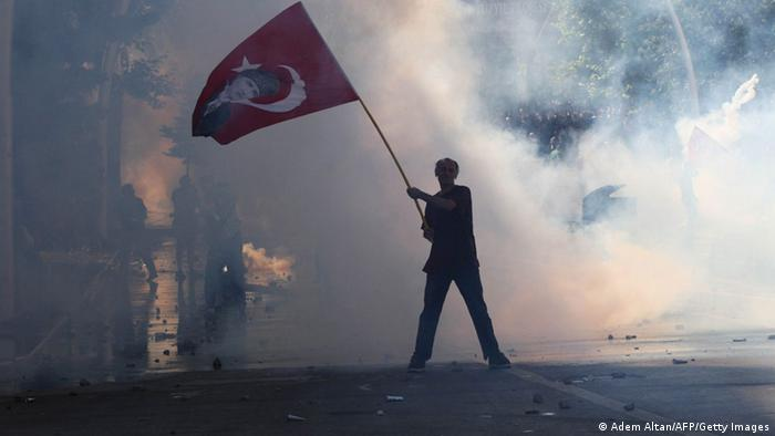 Against the smoky white backdrop of tear gas, a Turkish man waves a bright red Turkish flag defiantly. (Photo: ADEM ALTAN/AFP/Getty Images)