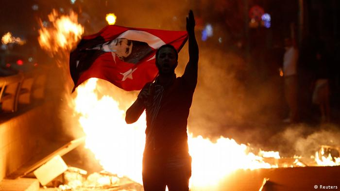 Backlit by a bright orange fire burning in a city, a man waves a red flag with his hands (Photo: Umit Bektas/REUTERS)