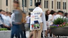 Man holding a sign with a picture of North Korean defectors (Reuters)