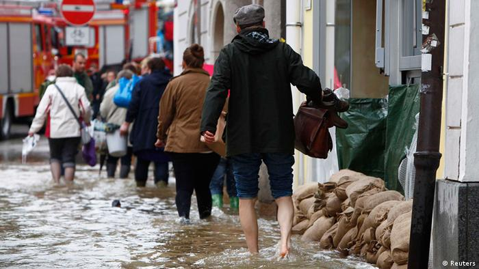 People walk through the flooded centre of the Bavarian town of Passau, about 200 km (125 miles) northeast of Munich June 3, 2013. Following heavy rain and thaw, the Inn and Donau rivers are expected to rise to over 11 meters. REUTERS/Michaela Rehle (GERMANY - Tags: DISASTER SOCIETY ENVIRONMENT)