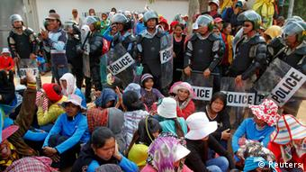 Garment workers sit beside police officers during a protest in front of a factory owned by Sabrina (Cambodia) Garment Manufacturing in Kampong Speu province, west of the capital Phnom Penh June 3, 2013. Several thousand workers protested and some clashed with police at the factory in Cambodia which makes clothing for U.S. sportswear company Nike, as they continue a protest refusing to give up their campaign for higher pay. REUTERS/Samrang Pring (CAMBODIA - Tags: BUSINESS TEXTILE CIVIL UNREST EMPLOYMENT CRIME LAW)