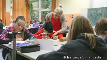 Lehramtsstudentin Arta Kolgeci erklärt Schüler Orcun bei ihrer ersten Unterrichtsstunde an der Oskar-Schindler-Gesamtschule Hildesheim seine Aufgabe (Foto: Isa Lange/Uni Hildesheim)
