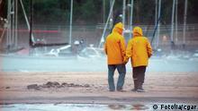 Zwei Menschen im gelben Regenmantel gehen am Strand spazieren