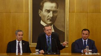 Turkey's Prime Minister Tayyip Erdogan, accompanied by his deputies Bulent Arinc (L) and Bekir Bozdag (R), speaks during a news conference at Ataturk International Airport in Istanbul June 3, 2013. Erdogan called for calm on Monday, after a weekend of fierce anti-government protests, urging people not to be provoked by demonstrations he said had been organised by extremist elements. REUTERS/Stringer (TURKEY - Tags: POLITICS)