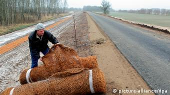 Ein Vorarbeiter wickelt eine Kokosmatte am neu entstandenen Oderdeich aus, um die Böschung vor Erosionen zu schützen. (Foto: picture alliance/dpa)