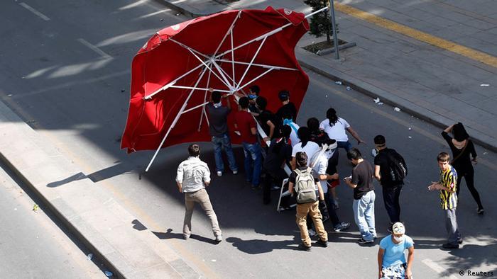 На фотографии видно, как с помощью большого зонта от солнца демонстранты в Стамбуле защищаются от водометов