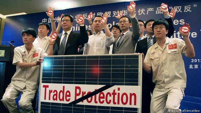 Chinese solar industry representatives holding anti-trade protection signs. (photo: dpa - Bildfunk)