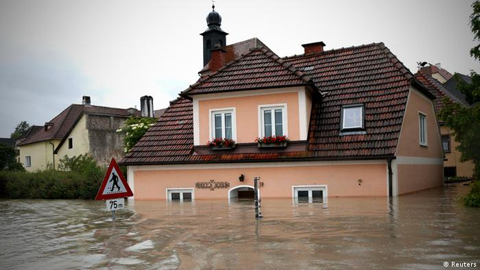 A house is partially submerged by flood water in the centre of the Austrian village of Emmersdorf, about 100 km (62 miles) west of Vienna June 3, 2013. Torrential rain in Tyrol, Salzburg, Upper and Lower Austria caused heavy flooding over the weekend, forcing people to evacuate their homes. REUTERS/Leonhard Foeger (AUSTRIA - Tags: DISASTER ENVIRONMENT)