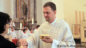A priest hands out a piece of altar bread (photo: Marc Herwig dpa)