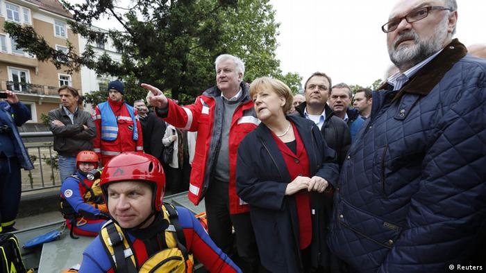 German politicians look off camera toward flood damage (Photo: REUTERS/Wolfgang Rattay)