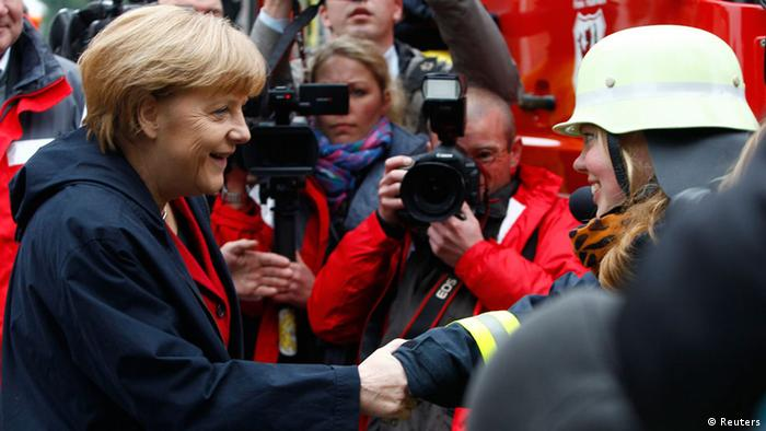 German Chancellor Angela Merkel (L) shakes hands with a firefighter during a visit to the south-eastern Bavarian town of Passau, about 200 km (124 miles) north-east of Munich June 4, 2013. Torrential rain in the south and south-east of Germany caused heavy flooding over the weekend, forcing people to evacuate their homes. REUTERS/Michaela Rehle (GERMANY - Tags: DISASTER ENVIRONMENT)