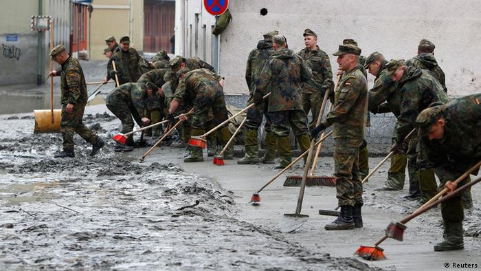 German army Bundeswehr soldiers clear the streets from mud before the visit of German Chancellor Angela Merkel to the south-eastern Bavarian city of Passau, about 200 km (124 miles) north-east of Munich June 4, 2013. Torrential rain in the south and south-east of Germany caused heavy flooding over the weekend, forcing people to evacuate their homes. REUTERS/Michaela Rehle (GERMANY - Tags: DISASTER ENVIRONMENT)
