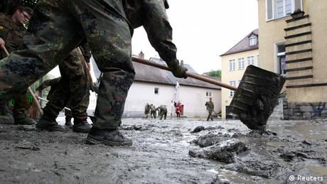 Men wearing battle dress uniforms use a snow shovel to pile up heaps of mud on a German street (Photo: Michaela Rehle/REUTERS)