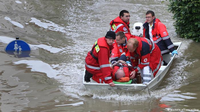 Five men wearing red jackets and riding in a boat take care of another man laying in the boat. (Photo: Karl-Josef Hildenbrand dpa)