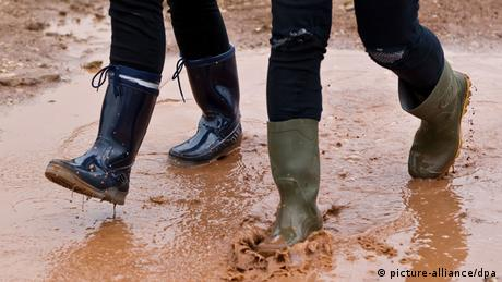 In a picture that shows only two sets of legs, the rubber boots go splashing through a brown puddle of water Photo: Daniel Karmann/dpa)