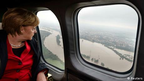 Chancellor Angela Merkel looks through the window of an airplane or helicopter toward floodwaters on the ground (Photo: Steffen Kugler/Reuters)