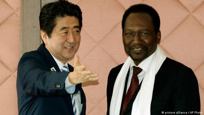 Japanese Prime Minister Shinzo Abe, left, shows the way to Mali's Interim President Dioncounda Traore during their bilateral meeting at the fifth Tokyo International Conference on African Development (TICAD) in Yokohama, south of Tokyo on Monday, June 3, 2013. (AP Photo/Toshifumi Kitamura, Pool)