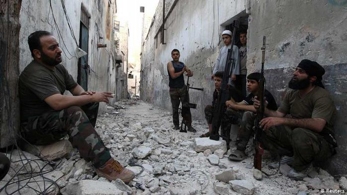 Members of the Free Syrian Army talk as they sit with their weapons in a damaged street in Aleppo's Karm al-Jabal district, June 3, 2013. REUTERS/Muzaffar Salman