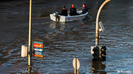 Traffic lights poke out from the water as a boat cruises by on a flooded street (Photo: Thomas Peter/REUTERS)