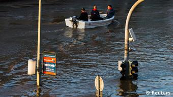 People ride in a boat on waters covering a flooded road in the eastern German city of Dresden, June 4, 2013. Torrential rain in the south and south-east of Germany caused heavy flooding over the weekend forcing people to evacuate their homes. REUTERS/Thomas Peter (GERMANY - Tags: DISASTER ENVIRONMENT)