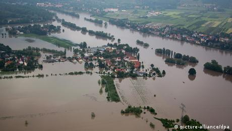 Portions of green land pop out from brown flood waters (Photo: Michael Kappeler/dpa)