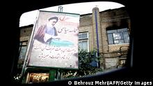A picture taken from inside a car shows a placard bearing a picture of the late founder of the Islamic Republic Ayatollah Ruhollah Khomeini, voting and a quote from him which reads in Persian 'My advice to the Iranians is to participate in all elections' in Sarcheshmeh street in downtown Tehran on June 4, 2013. AFP PHOTO/BEHROUZ MEHRI (Photo credit should read BEHROUZ MEHRI/AFP/Getty Images)